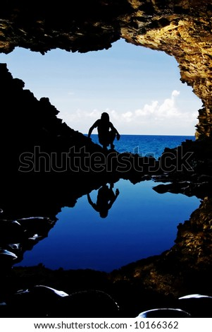 Reflection of a female figure in cave water