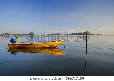 Reflection of a fisherman boat during a sunny day. - stock photo