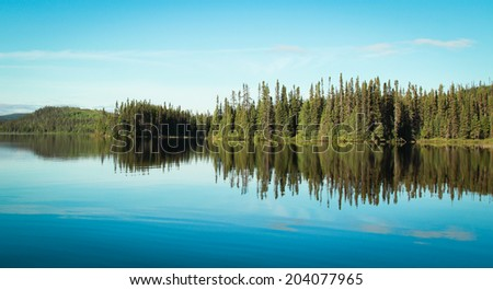 reflection of a forest into a calm lake in Quebec, Canada - stock photo