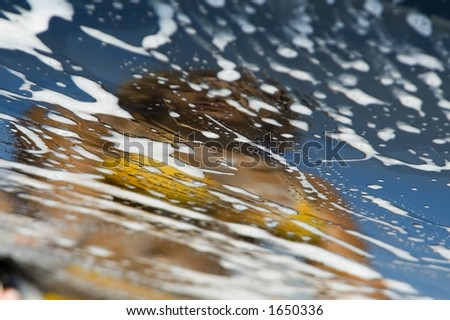 Reflection of a girl in a foamed car - stock photo