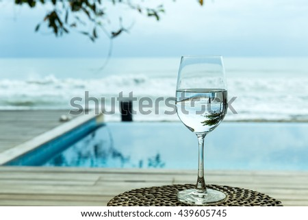 Reflection of a glass of water on beach front.