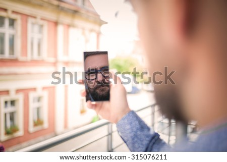 Reflection of a man's face in mobile phone - stock photo