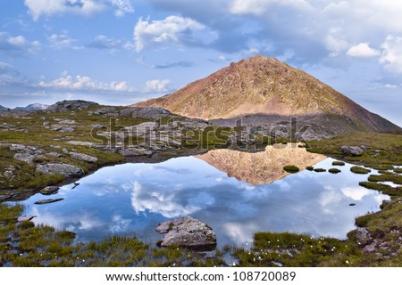 Reflection of a mountain and sky in a lake at high altitude. Crow Lake, Dolomites at sunset - stock photo