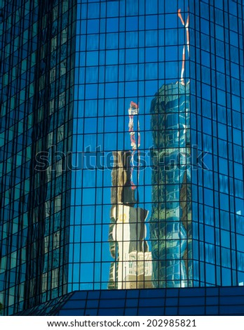 Reflection of a skyscraper  in the glass facade of another skyscraper, Frankfurt, Germany Office buildings in one of the most fascinating financial areas of Europe - stock photo