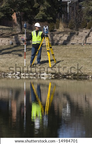 Reflection of a Surveyor working with robotic station - stock photo