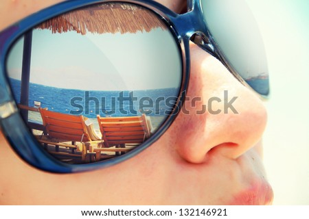 Reflection of a tropical resort in sunglasses - stock photo