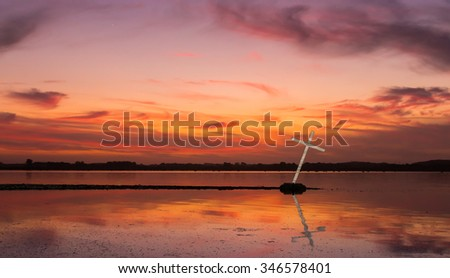 Reflection of a white cross on a lake as the sun goes down.