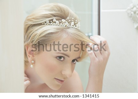 Reflection of a young bride fixing her hair