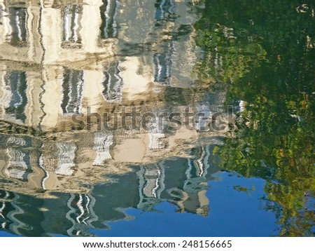 Reflection of apartment building and trees in the Canal St. Denis, Paris, France.