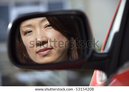 Reflection of Asian woman in side view car mirror. - stock photo