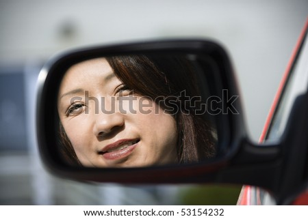 Reflection of Asian woman in side  view car mirror smiling. - stock photo