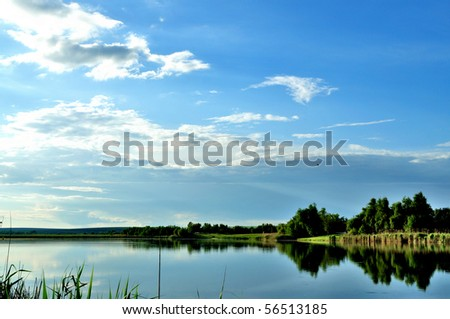 Reflection of blue sky with clouds in the lake - stock photo