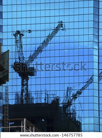 reflection of building construction on building mirror - stock photo