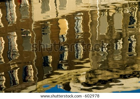 Reflection of canal houses in water - stock photo
