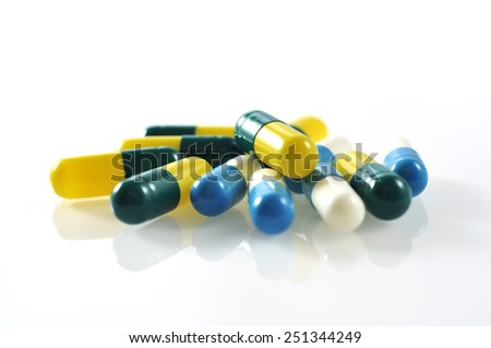 Reflection of Close Up Capsule Pills on White Background, Selective Focus - stock photo
