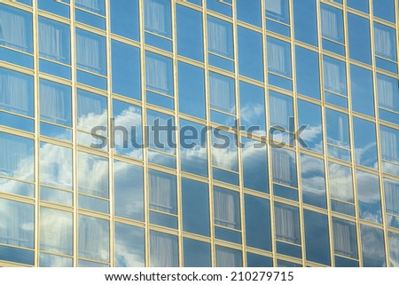 Reflection of clouds at building windows - stock photo