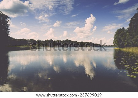 reflection of clouds in the lake with boardwalk and trees in background - retro, vintage style look