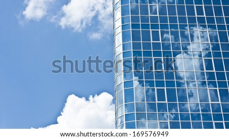 Reflection of clouds on skyscraper in the sunny day - stock photo