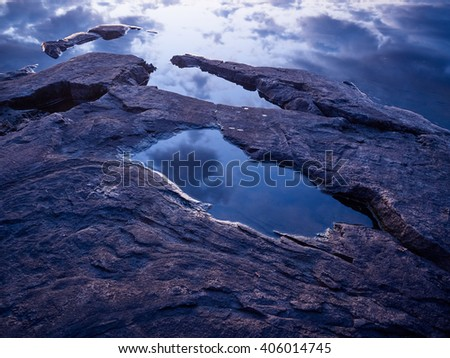 Reflection of cloudy blue sky between the rocks on the shore.  - stock photo