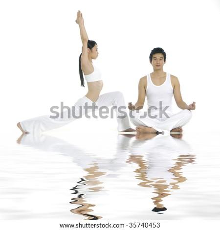 Reflection of couple doing yoga exercises together - stock photo