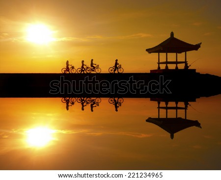 Reflection of cyclists riding on a concrete barrier in bali indonesia Sanur beach at sunrise. This is a great place to visit when you are in Bali .. - stock photo