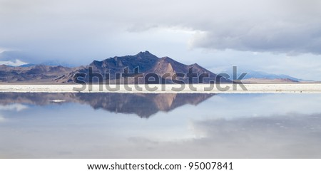 reflection of distant mountains in a pool in the Bonneville Salt Flats - stock photo