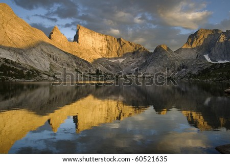 reflection of East Temple Peak and the Steeple in Deep Lake with evening alpenglow on the mountains, wind river range, wyoming - stock photo