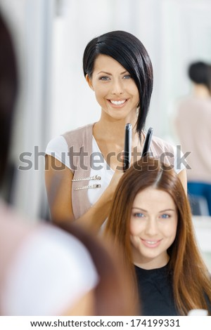 Reflection of hair stylist doing hair style for woman in hairdressing salon. Concept of fashion and beauty - stock photo