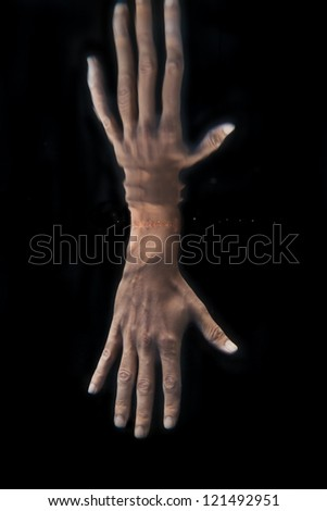 Reflection of hand in fresh water on black background - stock photo