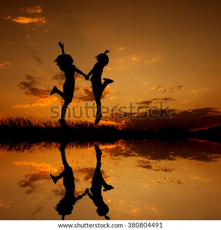 Reflection of Happy of two women friends jumping and sunset silhouette,water reflect with copy space. - stock photo