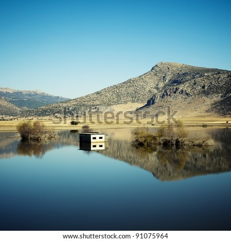 Reflection of hills, trees and house in lake , Antalya ( Grain Added ) - stock photo