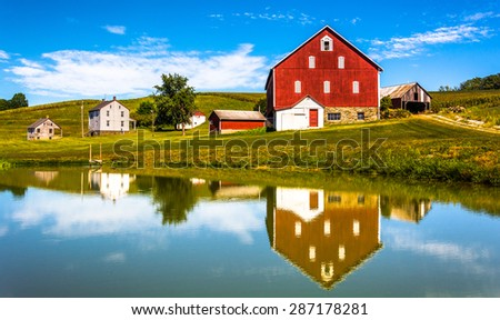 Reflection of house and barn in a small pond, in rural York County, Pennsylvania. - stock photo