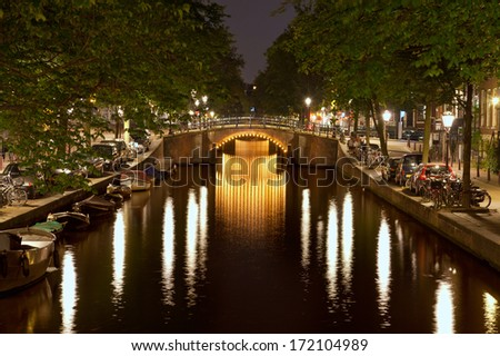 Reflection of illuminated bridges and street lights on the dark water surface of a canal in Amsterdam. - stock photo