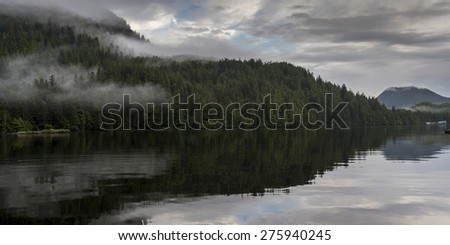 Reflection of landscape on water, Skeena-Queen Charlotte Regional District, Haida Gwaii, Graham Island, British Columbia, Canada - stock photo
