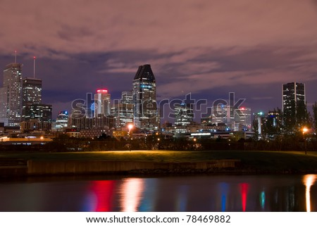Reflection of light from Buildings in Downtown Montreal in the Lachine Canal, and in the background, the City of Montreal at night. - stock photo