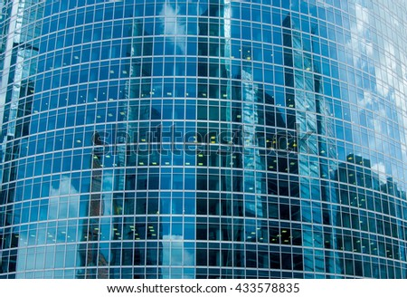 Reflection of many skyscrapers on a glass curved surface of another building. Modern downtown architecture. - stock photo
