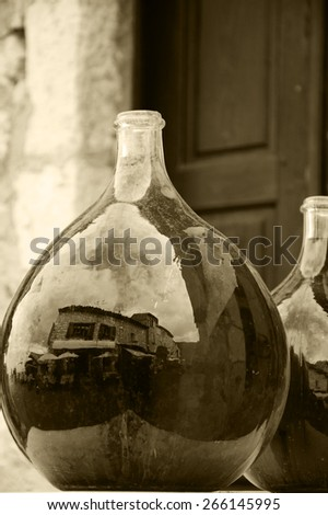 Reflection of medieval town street in big dirty bottles with colored liquid. Cityscape in bottle glass. (Provence France) Sepia aged photo. Selective focus on left bottle. - stock photo