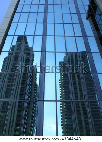 Reflection of modern glass skyscrapers in office block windows in London, England, UK - stock photo