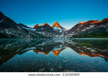 Reflection of mount Assiniboine on Magog lake at sunrise, Alberta, Canada - stock photo