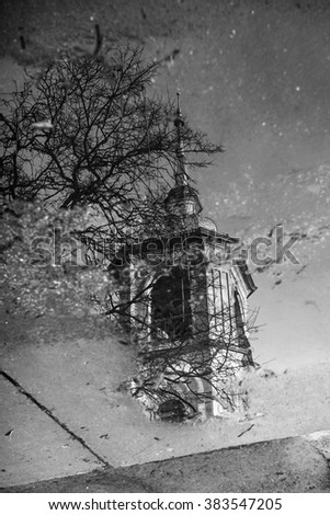 Reflection of old ortodox church bell tower puddle - stock photo