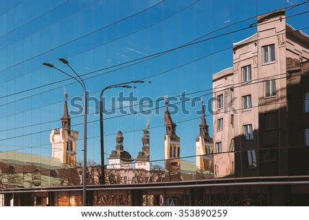 Reflection of old town in the modern glass building - stock photo