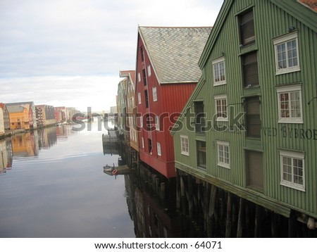 Reflection of old wharfside sheds along river Nidelva in Trondheim, Norway. - stock photo