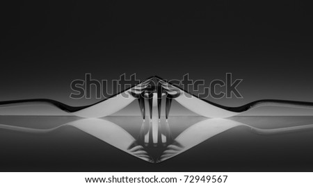 Reflection of one fork in two spoons like a tiger print - stock photo