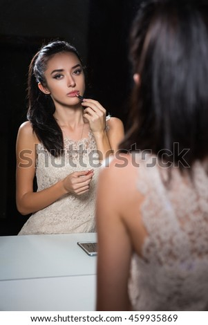 Reflection of pretty young brunette doing makeup - stock photo