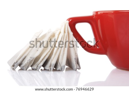 reflection of Red Ceramic cup with tea bags on white background - stock photo