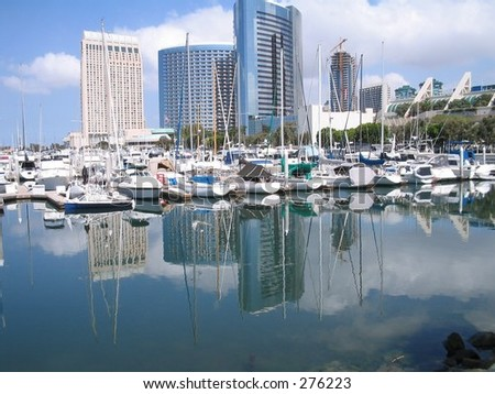 reflection of sailboats and city buildings in San Diego  harbor