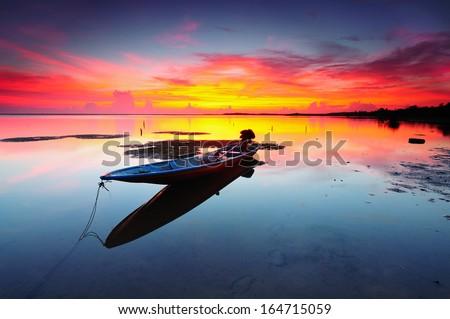 Reflection of Single Boat During Sunrise  - stock photo