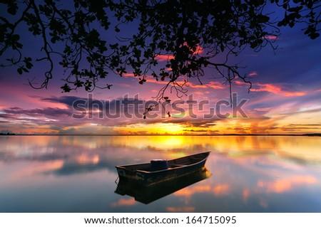Reflection of Single Boat During Sunrise under the Tree  - stock photo