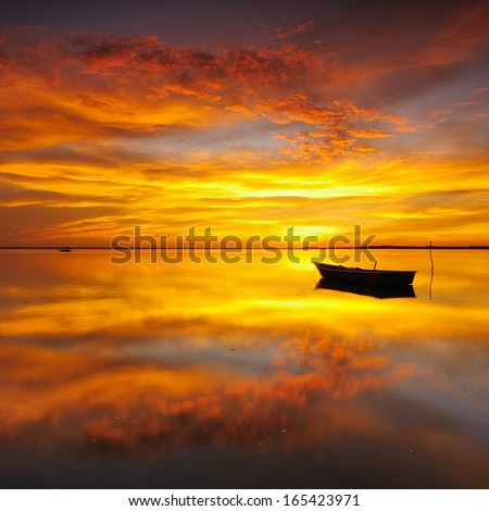 Reflection of Single Boat with Burning Sky During Sunrise/Sunset - stock photo
