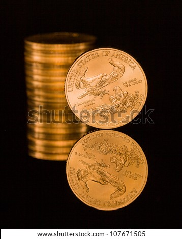 Reflection of single gold coin and stack on black polished surface - stock photo
